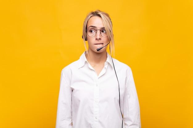 Operadora de telemarketing parecendo intrigada e confusa, mordendo o lábio com um gesto nervoso, sem saber a resposta para o problema