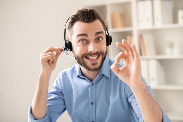 Operadora jovem e feliz com um sorriso cheio de dentes mostrando um gesto de aprovação enquanto olha para você e se comunica no fone de ouvido