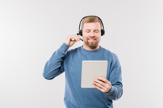 Operadora jovem e feliz usando um fone de ouvido, olhando para a tela do touchpad enquanto consulta clientes on-line de forma isolada
