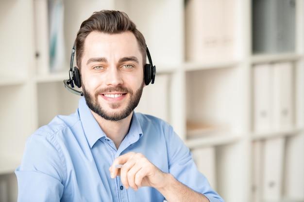 Operadora jovem sorridente com fone de ouvido olhando para você enquanto trabalha com as perguntas e dúvidas dos clientes no escritório