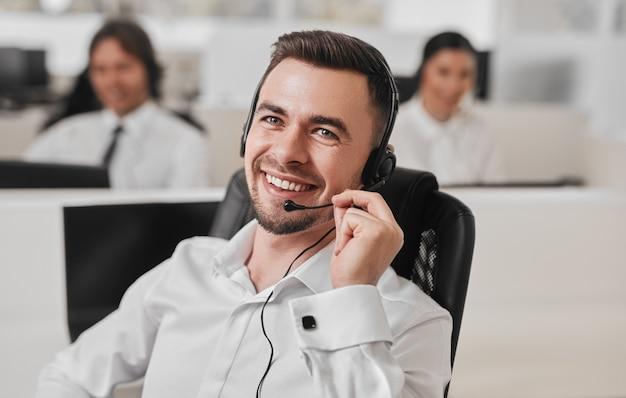 Operadora positiva com fone de ouvido atendendo chamada telefônica