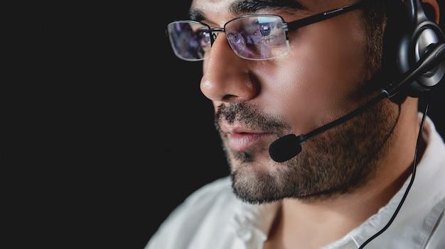 Operadores de serviço ao cliente asiático masculino trabalhando turno da noite no call center