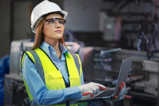 Operária de fábrica asiática segurando laptop e sorrindo também olha para a câmera na área de trabalho