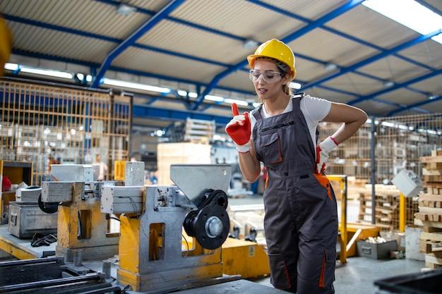 Operária de fábrica operando máquina industrial na linha de produção