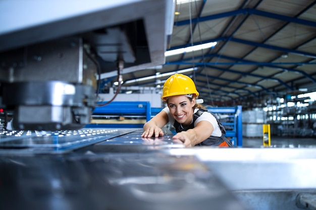 Operária feminina com uniforme de proteção e capacete operando máquina industrial na linha de produção