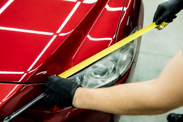 Operário aplicando fita protetora no carro