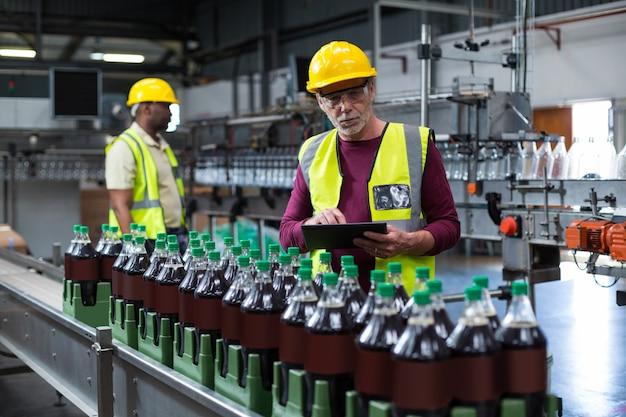 Operário com tablet digital monitorando linha de produção de bebidas