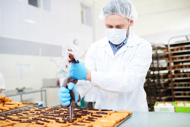 Operário de confeitaria decorando pastelaria usando saco de confeiteiro