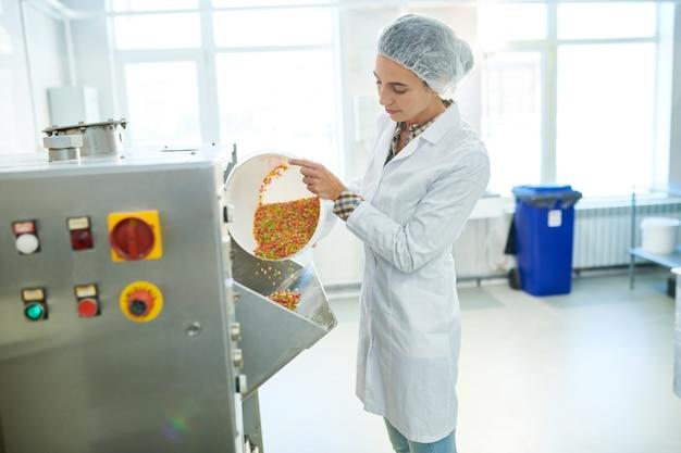 Operário de confeitaria derramando arco-íris polvilha na máquina