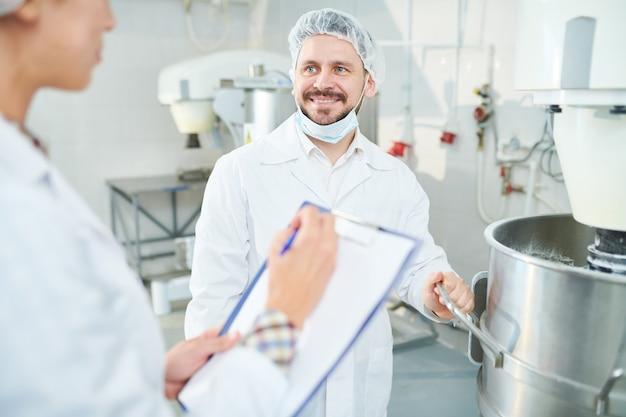 Operário de confeitaria e colega a tomar notas a sorrir