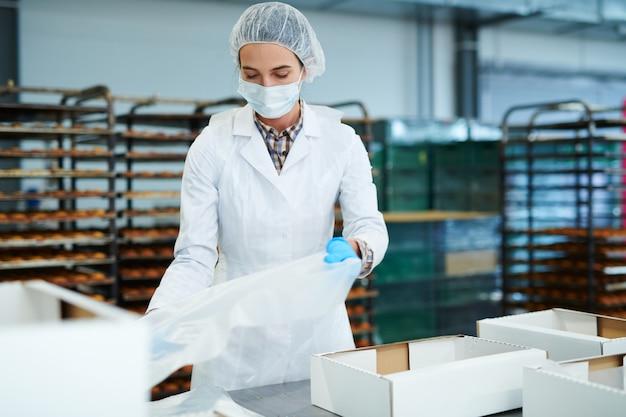 Operário de confeitaria preparando caixas vazias