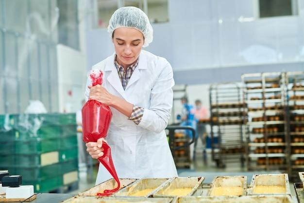 Operário de confeitaria usando saco de pastelaria