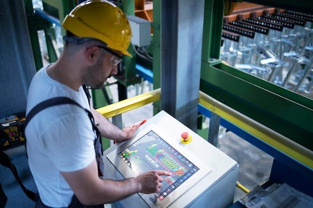 Operário de fábrica monitorando máquinas industriais e produção remotamente na sala de controle