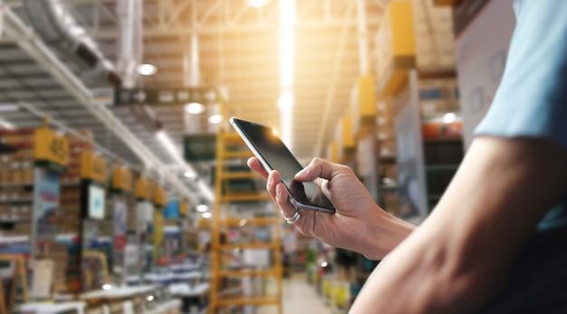 Operário de fábrica que usa o aplicativo no smartphone móvel para operacionalizar a automação para o comércio moderno.