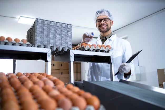 Operário de fábrica segurando a lista de verificação, inspecionando e verificando a qualidade dos ovos na fábrica de processamento de alimentos.