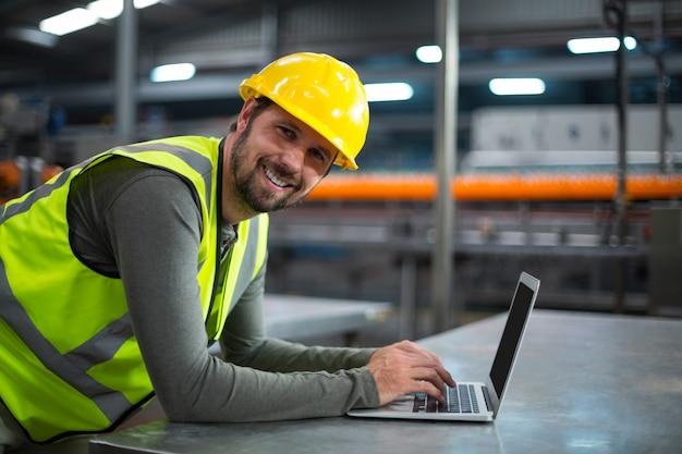 Operário de fábrica usando laptop
