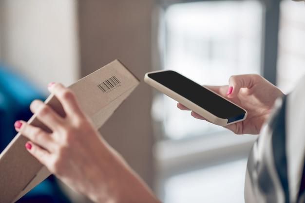 Operário de loja da internet digitalizando informações na embalagem do produto
