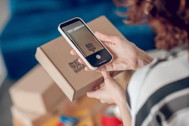 Operário de loja online digitalizando informações na embalagem do produto