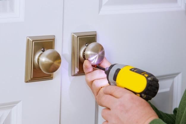Operário de serralheiro instalando uma nova fechadura fictícia em casa na porta