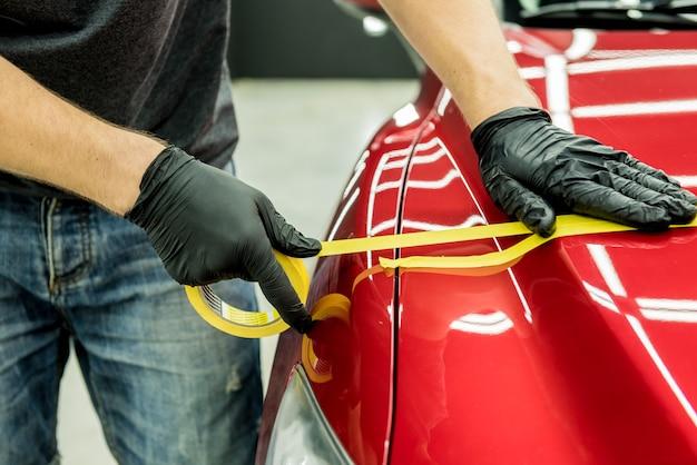 Operário de serviço automotivo aplicando fita protetora nos detalhes do carro antes de polir.