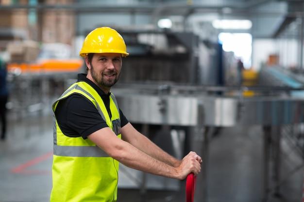 Operário de sorriso que puxa o carrinho na fábrica
