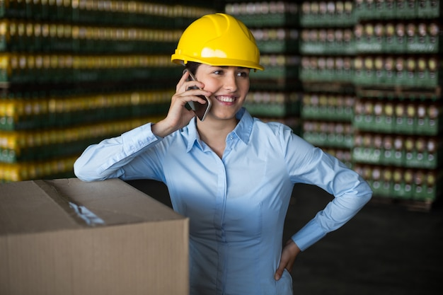 Operário feminino falando no celular