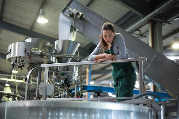 Operário feminino inspecionando um tanque de armazenamento