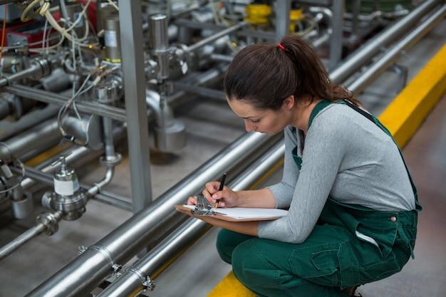 Operário feminino, mantendo o registro na área de transferência na fábrica