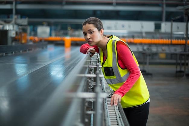 Operário feminino, verificando a correia transportadora