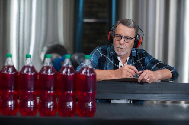 Operário masculino que monitora garrafas de bebida gelada