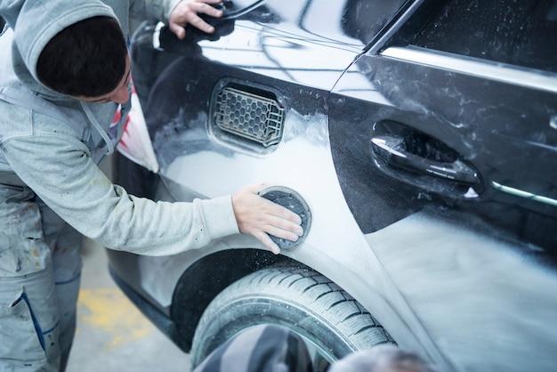 Operário mecânico, lixando, polindo a carroceria do carro e preparando o automóvel para pintar na garagem da oficina