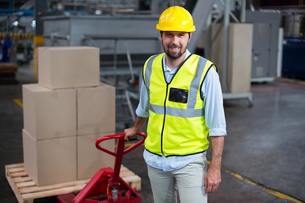 Operário puxando o carrinho de caixas de papelão na fábrica