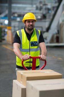 Operário puxando o carrinho de caixas de papelão