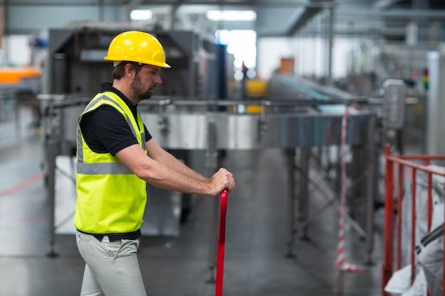 Operário puxando o carrinho na fábrica