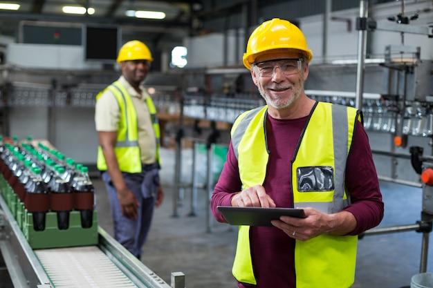 Operário sorridente com tablet digital em pé perto da linha de produção