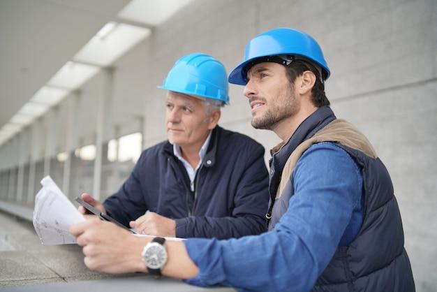 Operários de consultoria sobre a planta na visão do edifício moderno