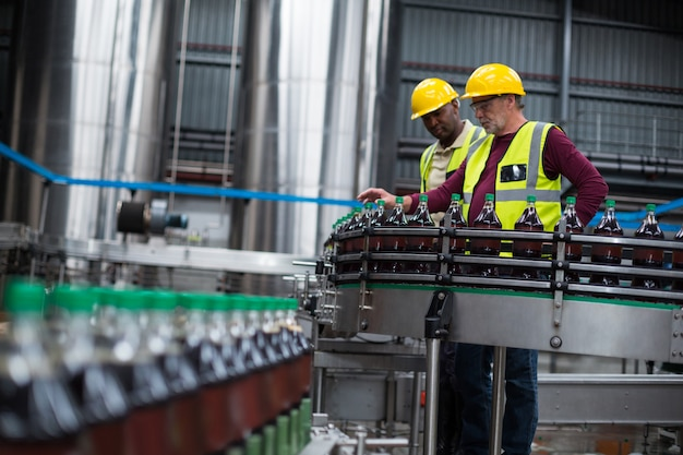 Operários monitorando garrafas de bebida gelada na fábrica de bebidas