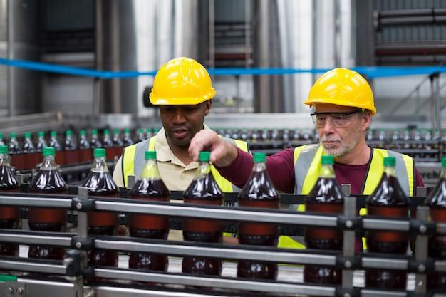 Operários que monitoram a linha de produção de bebidas