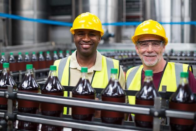 Operários sorridentes, monitorando a linha de produção de bebidas