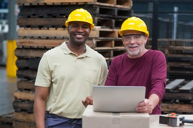 Operários trabalhando no laptop na fábrica de bebidas