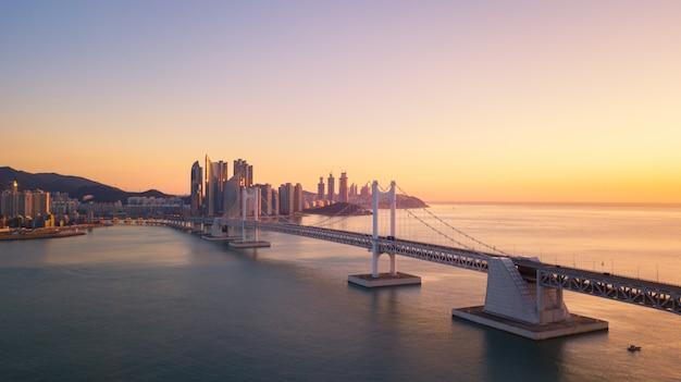 Opinião aérea da ponte e do haeundae de gwangan no nascer do sol, busan, coreia do sul.