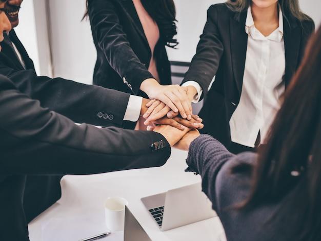 Opinião alta do anjo da equipe do negócio das mãos na sala de reunião, conceito dos trabalhos de equipa.