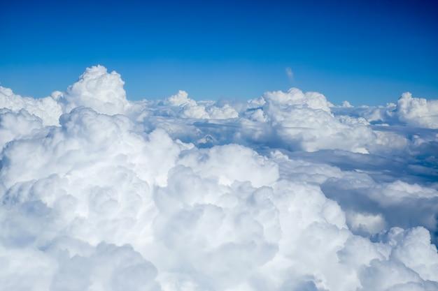 Opinião bonita da nuvem e do céu azul do avião da janela.