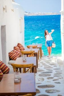 Opinião bonita do mar no café exterior mykonos em ilhas de cyclades.
