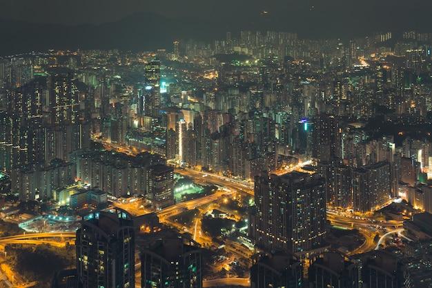Opinião da cidade da noite de uma altura aos edifícios nas luzes e nas estradas da cidade. hong kong.