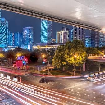 Opinião da cidade na noite com luz do tráfego e da fuga.