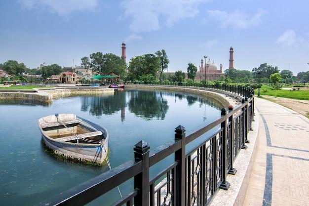 Opinião da mesquita de badshahi com o barco do lago fora no maior parque iqbal