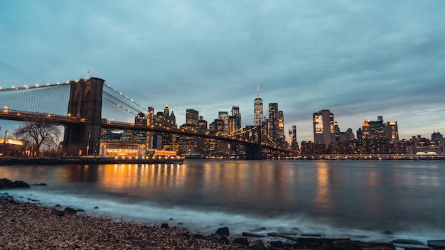 Opinião da noite da arquitectura da cidade da ponte de brooklyn e das construções em manhattan new york city, estados unidos.