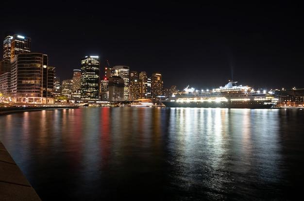 Opinião da noite da cidade e do navio de cruzeiros coloridos perto da ponte do porto em sydney, austrália.