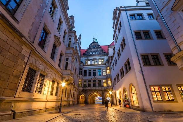Opinião da noite da rua estreita iluminada com construções históricas velhas da cidade de dresden, alemanha.